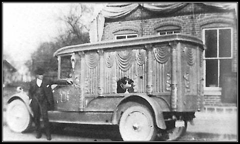 L.O. Wertenberger & his first motorized hearse in 1925  in front of Laketon Harware Store